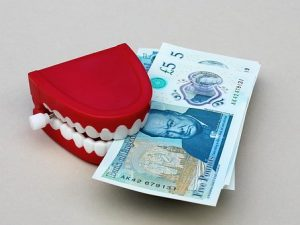 Plastic toy of fake teeth biting on pension money